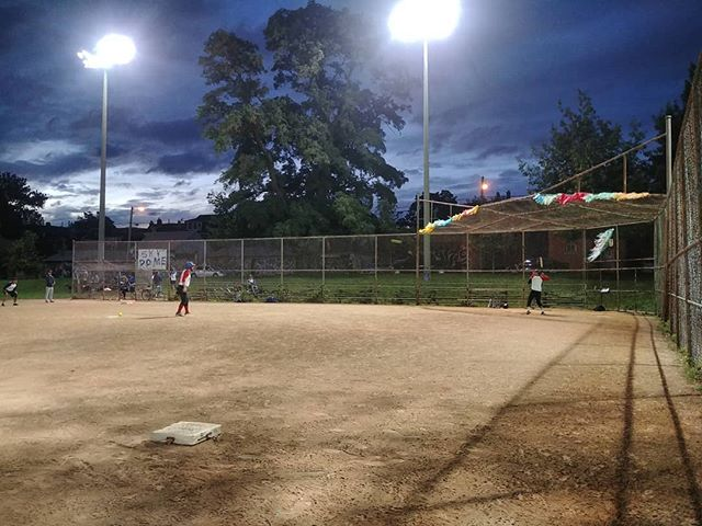 """Evening at the diamond, with pitcher and hitter in view and a sign with the words """"Sky Dome"""" spray-painted and attached to the diamond fences. Taken from behind third base."""
